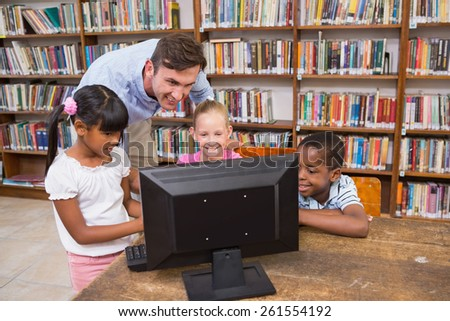 Teacher and pupils using computer at library at elementary school - stock photo