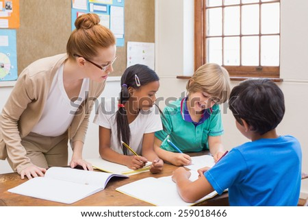 Teacher and pupils working at desk together at the elementary school - stock photo