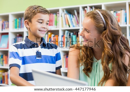 Teacher and school boy using laptop in library at school