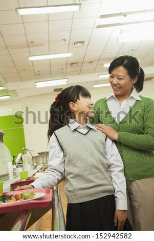 Teacher and school girl portrait in school cafeteria - stock photo