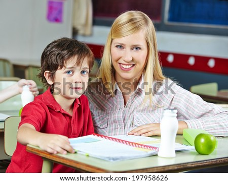 Teacher and student in classroom of an elementary school - stock photo