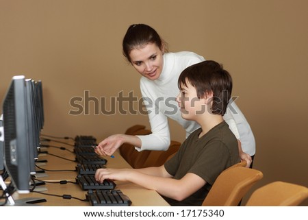 Teacher and student in computer lab - stock photo