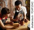 Teacher and student potters at workshop - stock photo