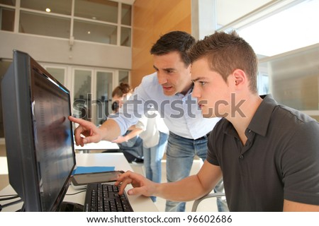 Teacher and student working on computer - stock photo