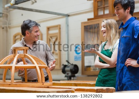 Teacher and students standing in a woodwork class and having fun - stock photo