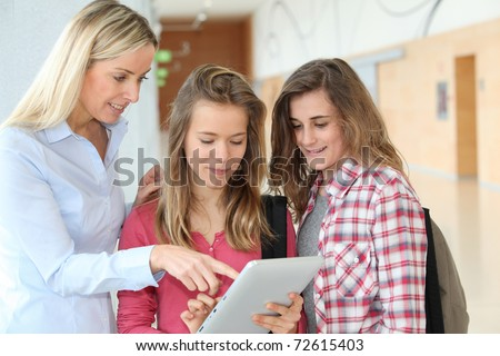 Teacher and teenage girls using electronic tablet - stock photo