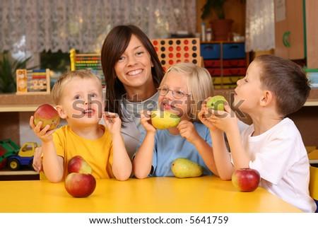 teacher and three preschoolers having break for fruit - stock photo