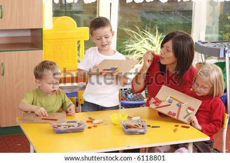 teacher and three preschoolers playing with wooden blocks - stock photo