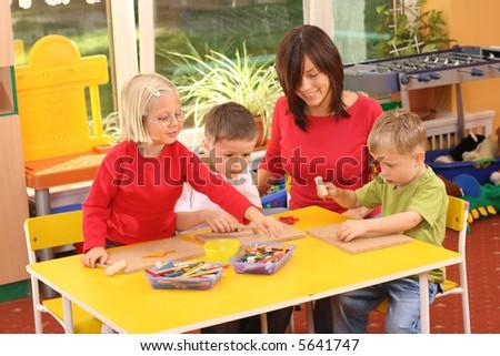 teacher and three preschoolers plazing with wooden blocks - stock photo