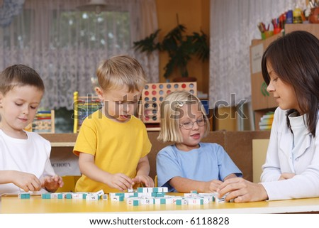 teacher and 5-6 years old girl and boys learning with letters