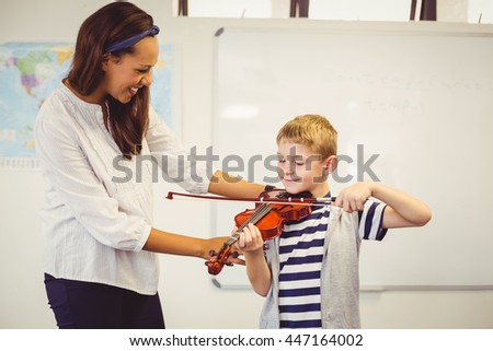 Teacher assisting a schoolboy to play a violin in classroom at school - stock photo