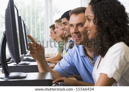 Teacher assisting college student in a computer lab - stock photo