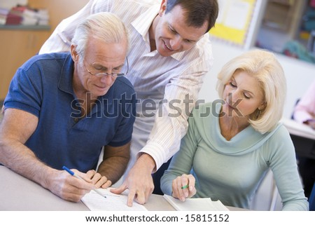 Teacher assisting mature student in class - stock photo