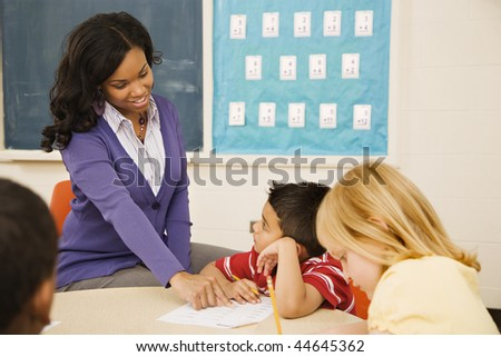 Teacher assisting young male student with lesson as he listens intently. - stock photo