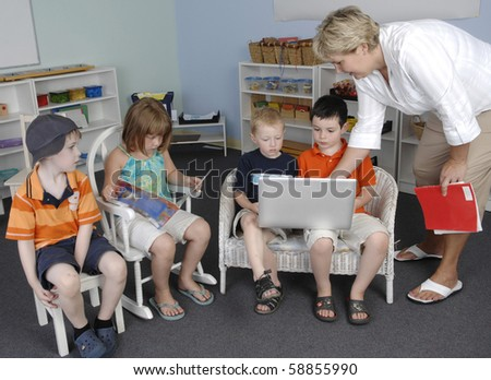 Teacher assists children with a work on the laptop computer at the preschool class. - stock photo