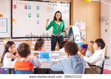 Teacher at the front of class with elementary school kids - stock photo