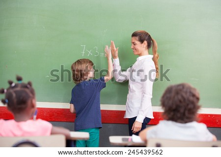 Teacher congratulating with kid in primary classroom. - stock photo