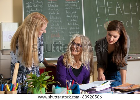 Teacher explaining something to two of her students - stock photo