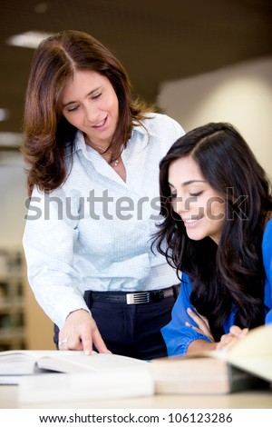 Teacher explaining the subject to a female student - stock photo