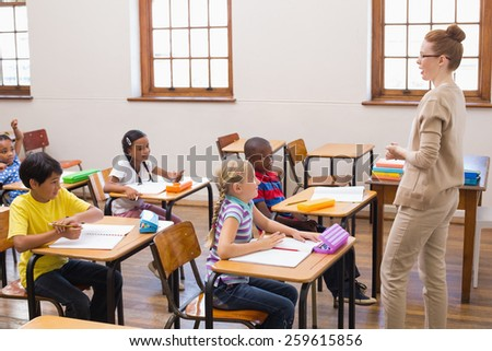 Teacher giving a lesson in classroom at the elementary school - stock photo