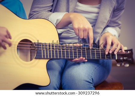 Teacher giving guitar lessons to pupil in a classroom - stock photo
