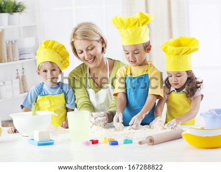 Teacher having fun with children backing in preschool activity - stock photo
