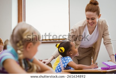 Teacher helping a little girl during class at the elementary school - stock photo