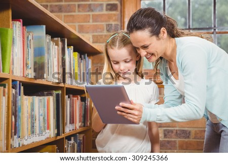 Teacher helping a student use a tablet at the elementary school - stock photo