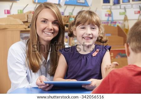 Teacher Helping Elementary School Pupil To Use Digital Tablet - stock photo