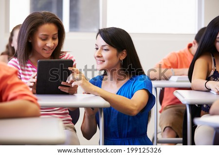 Teacher Helping Female High School Student In Classroom - stock photo
