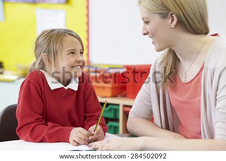 Teacher Helping Female Pupil With Practising Writing At Desk