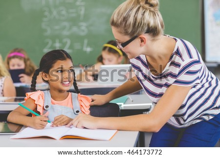 Teacher helping kids with their homework in classroom at school