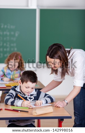 Teacher helping student one on one at the classroom - stock photo