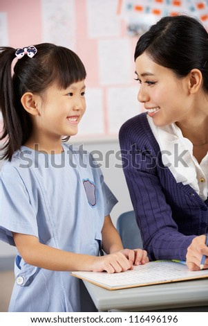 Teacher Helping Student Working At Desk In Chinese School Classroom