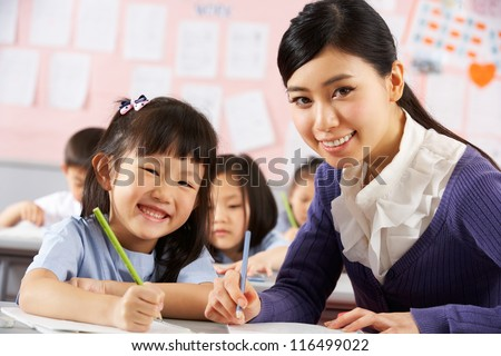 Teacher Helping Student Working At Desk In Chinese School Classroom - stock photo