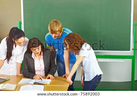 Teacher helping students who are standing around her in school classroom. - stock photo