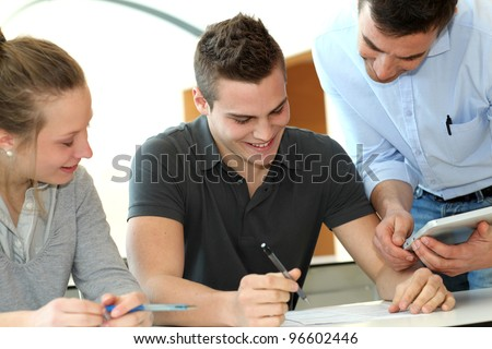 Teacher helping students with assignment - stock photo