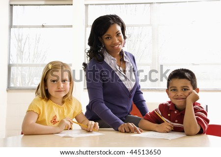 Teacher helping students with schoolwork in school classroom. Horizontally framed shot. - stock photo