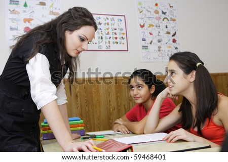 Teacher helping the students to get the answer right - stock photo