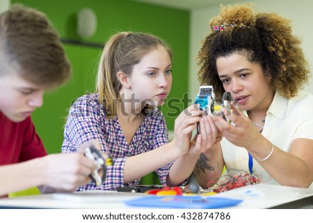 Teacher helping two students build a robotic arm in their design and technology lesson - stock photo