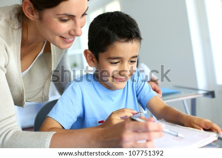 Teacher helping young boy with writing lesson - stock photo