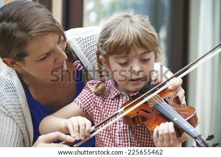 Teacher Helping Young Female Pupil In Violin Lesson - stock photo
