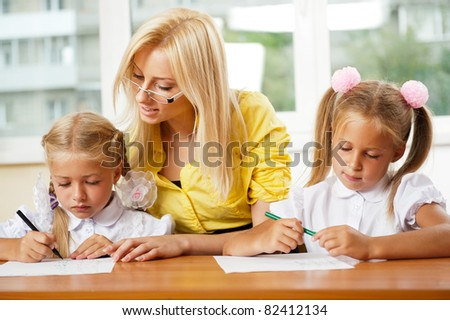 Teacher helps to little girls to make an exercises in classroom - stock photo