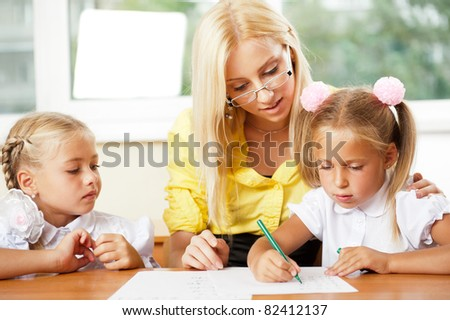 Teacher helps to little girls to make an exercises in classroom