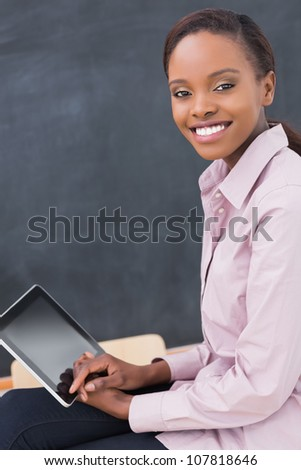 Teacher holding a tablet computer while smiling in a classroom - stock photo