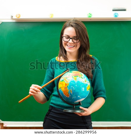 Teacher holding globe in hand - stock photo