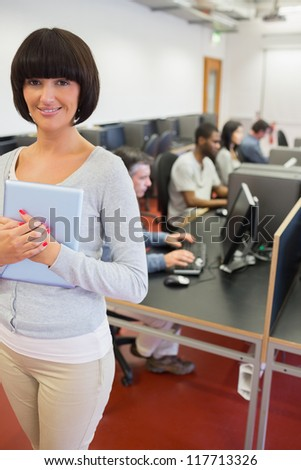 Teacher holding tablet pc in computer class in college - stock photo