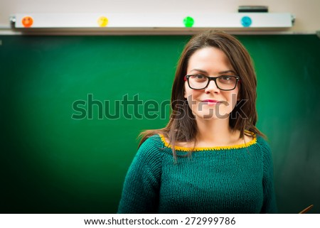 teacher in classroom near blackboard - stock photo