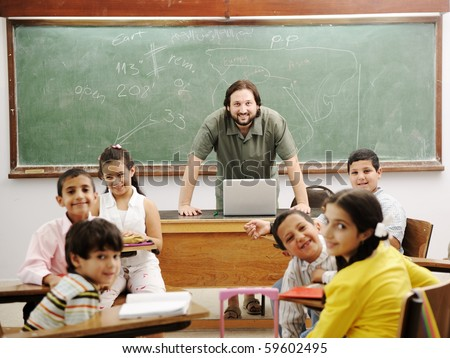 Teacher in classroom with his little happy students - stock photo