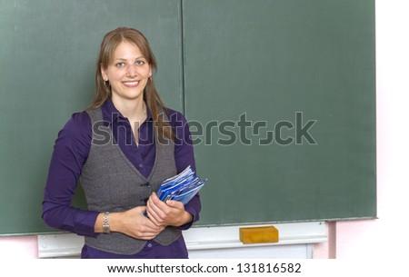 Teacher in front of a blackboard. - stock photo